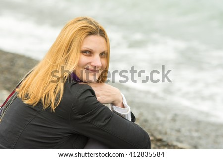 Portrait of sitting on the beach smiling young woman in cold weather