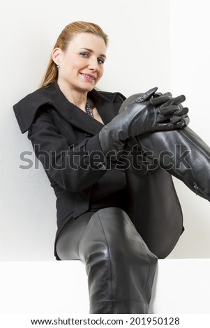 portrait of sitting woman wearing black clothes and boots - stock photo