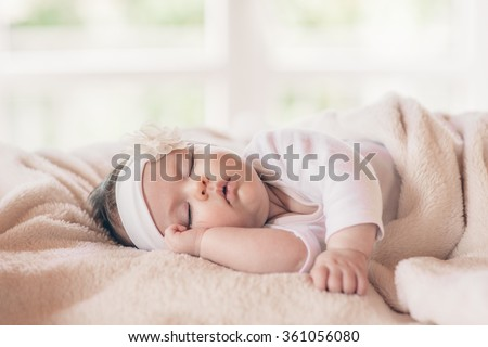 Portrait of sleeping baby in home and window is behind - stock photo