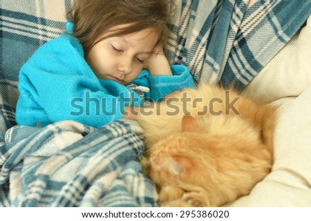 Portrait of sleeping cute little girl with a red cat at home
