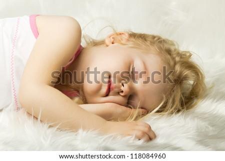 portrait of sleeping little girl in bed - stock photo