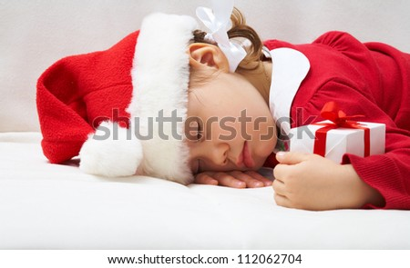 Portrait of sleeping little girl with Christmas present - stock photo