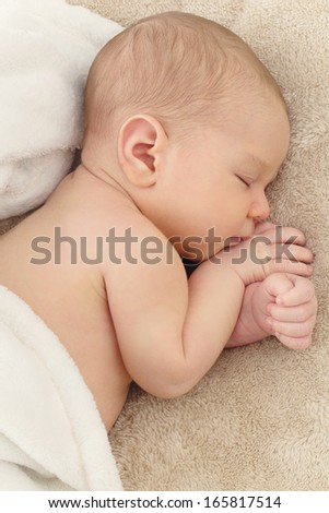 Portrait of sleeping newborn baby on beige cover