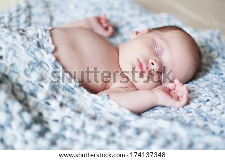 Portrait of sleeping newborn child hidden blanket  - stock photo