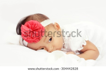 Portrait of sleepy baby lying in bed over white background with soft color tone - stock photo