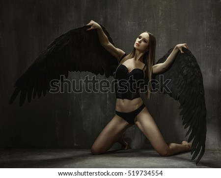 Portrait of slim young girls with big black wings who kneels on the background of gray concrete wall.