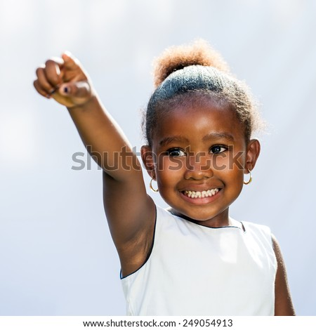 Portrait of small African girl pointing with finger into distance.Isolated against light background.