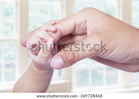 Portrait of small baby hand grasping the father's finger in the bedroom at home - stock photo