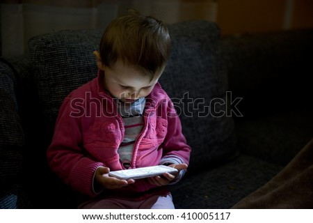 Portrait of small baby using smart-phone in dark living room