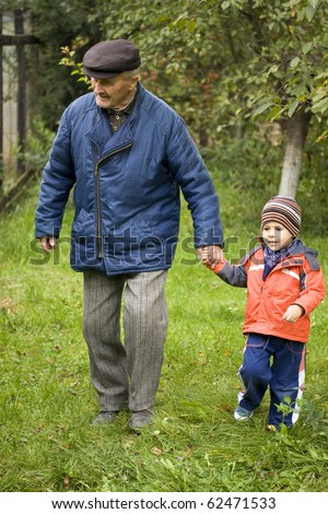 Portrait of small boy helping a old man on walking - Outdoor - stock photo