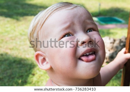 Portrait of small boy in a park in a summer day