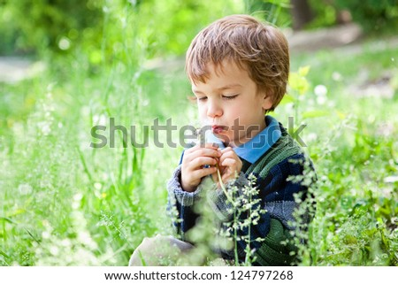 Portrait of small boy sitting on grass in park - stock photo