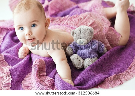 Portrait of small cute girl with blue eyes in her cozy violet bed. With teddy bear. Lovely toy - stock photo