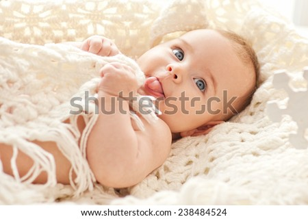 Portrait of small cute girl with blue eyes in her cozy white bed. - stock photo