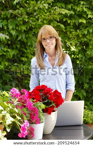 Portrait of small flower shop owner using laptop to take orders for her store. Business people. - stock photo