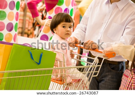 Portrait of small girl sitting in handcart while shopping with her parents - stock photo