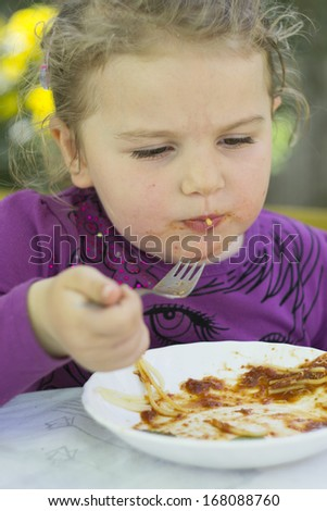 portrait of small girl while eating spaghetti  - stock photo