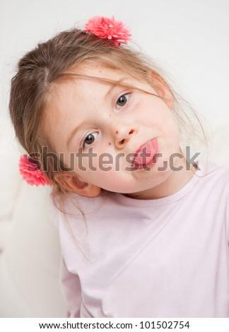 Portrait of small girl with chickenpox pointing tongue - stock photo