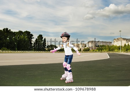 portrait of small little caucasian blond girl skating outside on stadium track in protective helmet