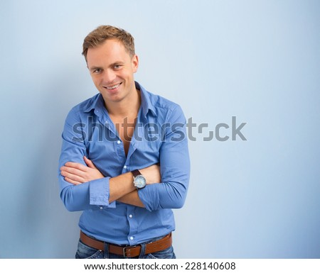Portrait of smart and confident handsome man standing against blue background - stock photo