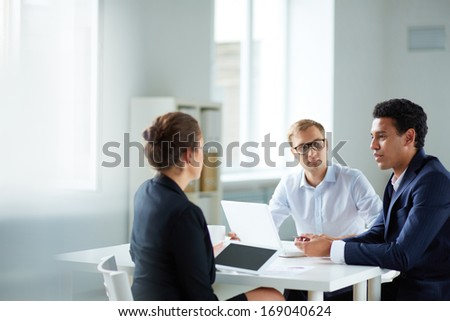 Portrait of smart business partners communicating at meeting - stock photo