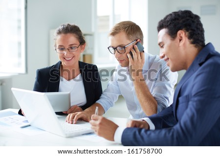Portrait of smart business partners using laptop at meeting, one of them speaking on the phone - stock photo