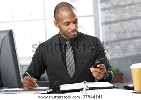 Portrait of smart businessman busy working at desk, using mobile phone, taking notes, concentrating . - stock photo