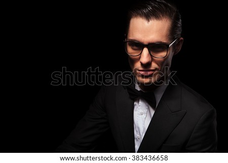 portrait of smart businessman in black suit posing in dark studio background while wearing glasses - stock photo