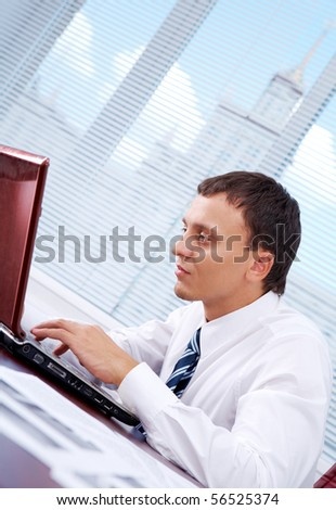 Portrait of smart businessman typing at workplace - stock photo
