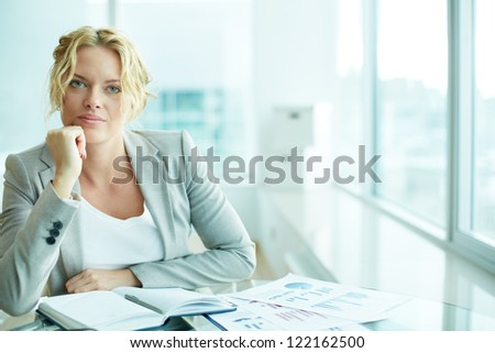 Portrait of smart businesswoman looking at camera while planning work - stock photo