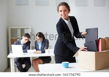 Portrait of smart businesswoman packing her things and looking at camera on background of working colleagues - stock photo