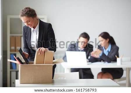 Portrait of smart businesswoman packing her things on background of working colleagues