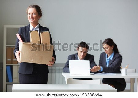 Portrait of smart businesswoman with box looking at camera on background of working colleagues - stock photo