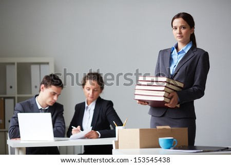 Portrait of smart businesswoman with stack of books looking at camera on background of working colleagues - stock photo