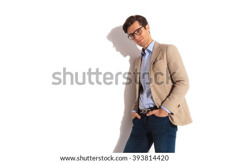 portrait of smart casual man leaning on the wall with both hands in pockets while posing for the camera in isolated studio background - stock photo