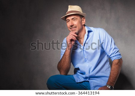 portrait of smart casual mature man seated in studio background looking away and touching chin - stock photo