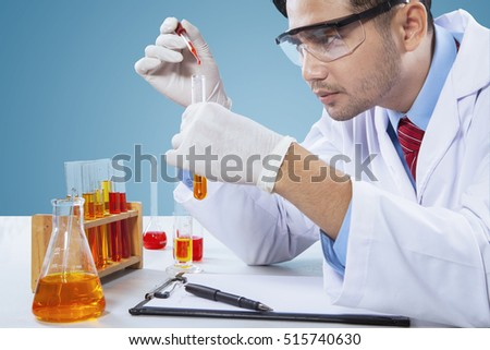 Portrait of smart chemist doing science experiment by using chemical liquid