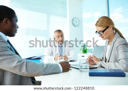Portrait of smart employees and their boss on background at meeting - stock photo
