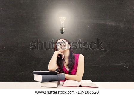 Portrait of smart female college student with books and a light bulb above her head as a symbol of bright ideas - stock photo