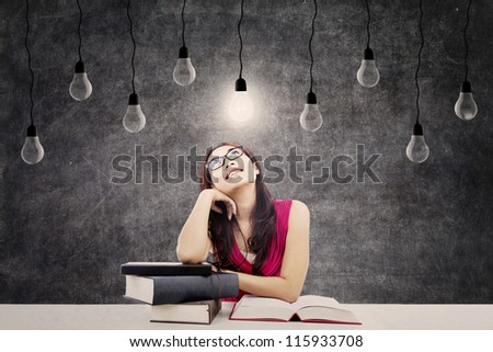 Portrait of smart female college student with books and bright light bulb above her head as a symbol of bright ideas - stock photo