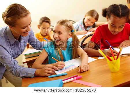 Portrait of smart girl and her teacher looking at each other at lesson in classroom - stock photo