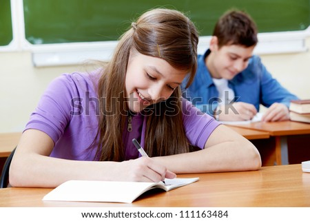 Portrait of smart girl at workplace writing with her classmate on background - stock photo