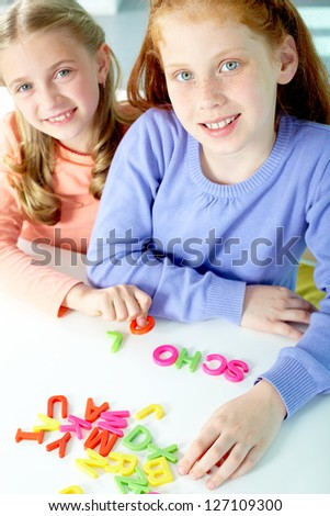 Portrait of smart girls making word �¢??school�¢?? and looking at camera - stock photo