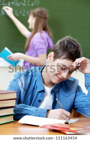 Portrait of smart guy looking into copybook in working environment - stock photo