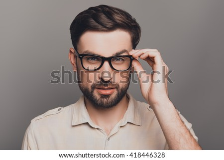 Portrait of smart handsome bearded man touching his glasses