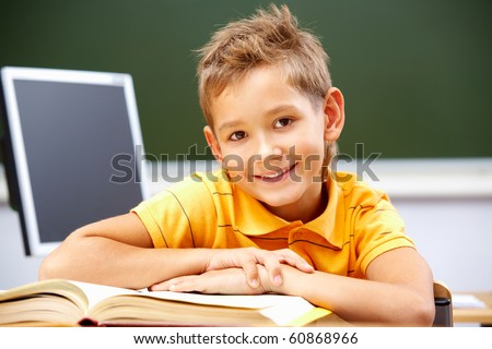 Portrait of smart lad at his place looking at camera during reading lesson - stock photo