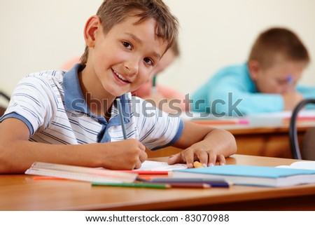 Portrait of smart lad at workplace with classmates on background - stock photo