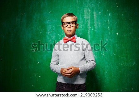 Portrait of smart lad in eyeglasses standing by the blackboard and looking at camera