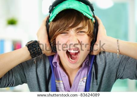 Portrait of smart lad in headphones looking at camera - stock photo