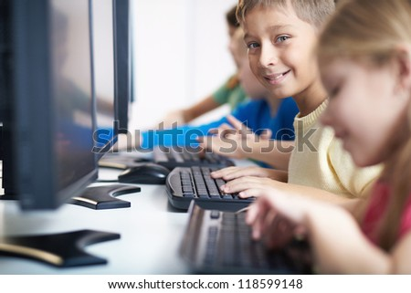 Portrait of smart lad looking at camera at computer lesson - stock photo
